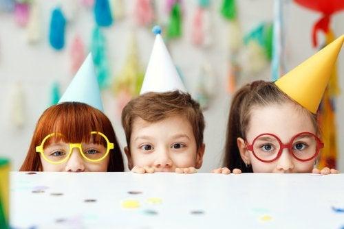 Niños celebrando un cumpleaños con gorros y confeti.