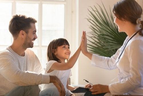 Niña chocando la mano con su pediatra tras una revisión.