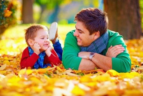 Padre e hijo hablando tumbados en las hojas secas del suelo.