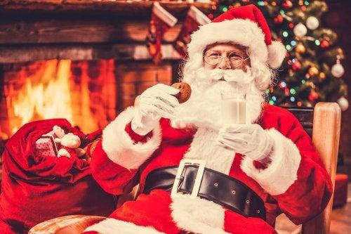 Papá Noel comiendo galletas y leches frente a una chimenea.