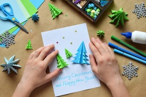 Decorando las tarjetas de Navidad con árboles hechos con cartulina.