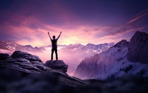 Hombre conquistando la cima de una montaña como un nuevo renacer.