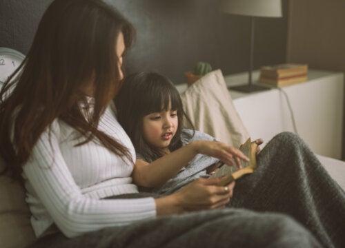 Madre leyendo a su hija un libro antes de dormir.