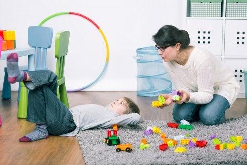 Madre intentando que su hijo recoja los juguetes de su habitación.