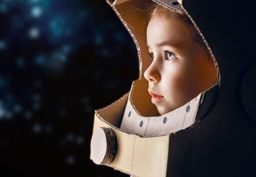 Niña con un casco de astronauta hecho con cartón después de haber leído algunos de los libros infantiles para pequeños astronautas.
