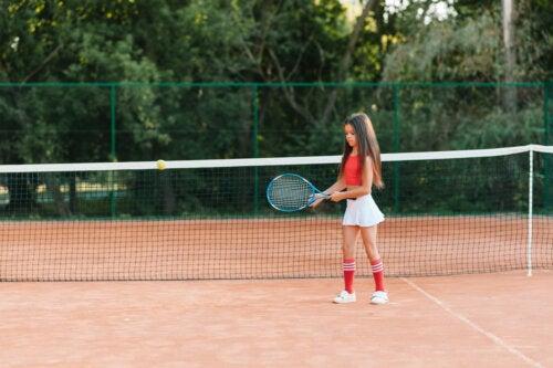 Niña jugando al tenis tras haber leído algunos libros infantiles sobre deporte.