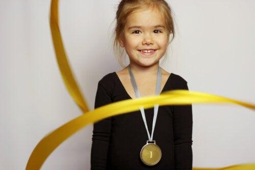 Niña con una medalla de gimnasia rítmica tras haber leído algunos libros infantiles sobre las Olimpiadas.