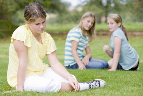 Niña sentada sola en el césped porque no tiene amigos.