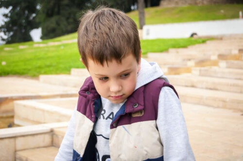 Niño con baja autoestima y síndrome de Solomon sentado pensativo.