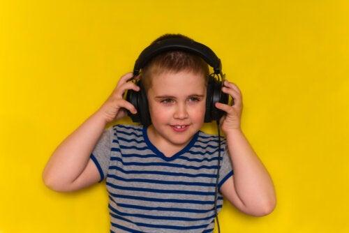 Niño escuchando canciones infantiles en inglés con los auriculares.