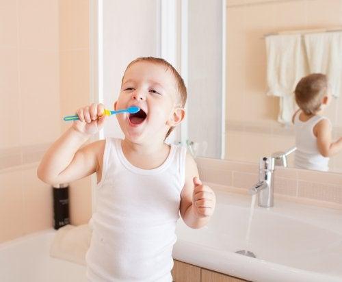 Niño contento mientras aprender a lavarse los dientes.