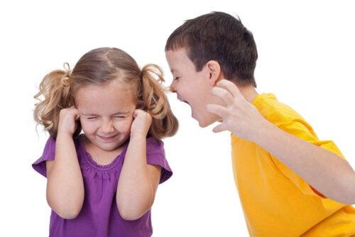 Niño con mal comportamiento gritando a su hermana.