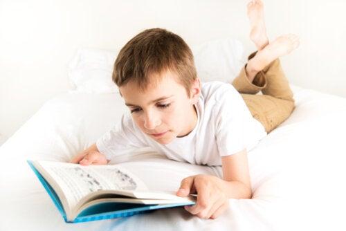 Niño leyendo uno de los libros de la Serie Roja de El Barco de Vapor en su cama.
