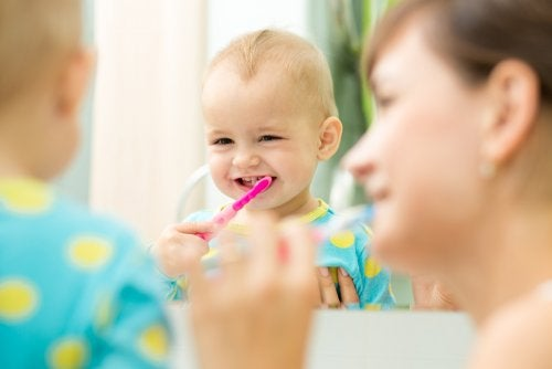 Niño con su madre aprendiendo a lavarse los dientes.