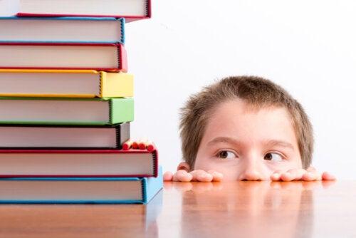 Niño asustado mirando una pila de libros.