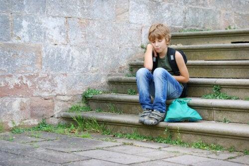 Niño sentado en unas escaleras pensando.