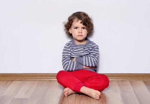 Niño sentado de brazos cruzados mostrando su negatividad ante la vida.