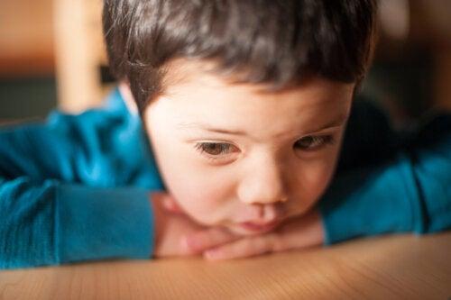 Niño triste y pensativo apoyado en la mesa.