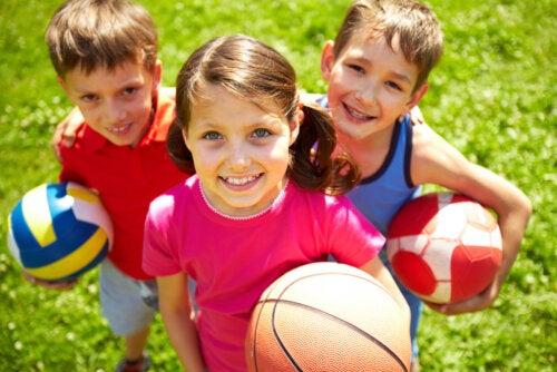 Niños con balones y pelotas de diferentes deportes.