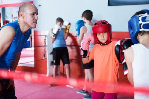Niños practicando boxeo, uno de los deportes de combate, con su entrenador.
