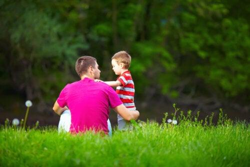 """Padre hablando con su hijo en el campo y aprendiendo a decir """"no"""" a los hijos para su educación."""