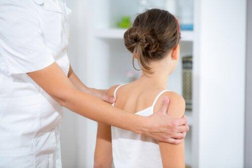 Chica con problemas de espalda en la consulta del médico durante la adolescencia.