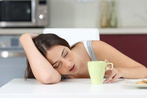Adolescente medio dormida mientras se toma un café por la mañana.