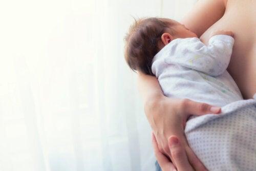 Bebé mamando del pecho de su madre durante la lactancia.