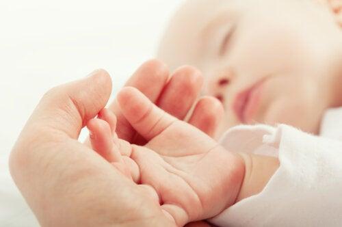 Madre agarrando la mano de su bebé.
