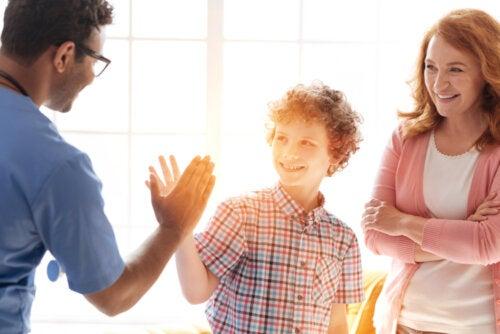 Adolescente chocando la mano con el médico tras la consulta.