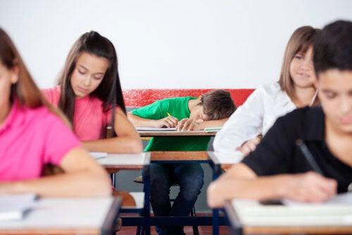 Chico dormido en clase porque es uno de los adolescentes vespertinos.