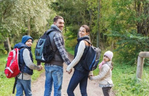 Familia de excursión por el campo y teniendo muy en cuenta las cosas que no pueden faltar en la mochila.