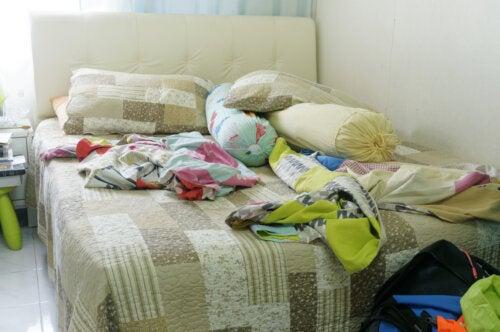 Cama llena de ropa en una habitación desordenada.