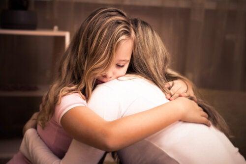 Madre abrazando a su hija siendo una madre consciente.