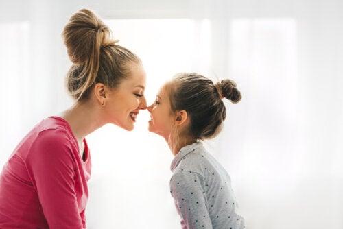 Madre e hija dándose un beso de esquimal tras tener en cuenta el valor educativo de la serenidad.
