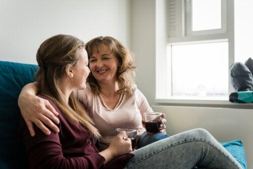 Madre hablando con su hija adolescente mientras se toman un té.
