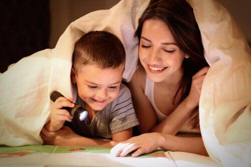 Madre e hijo leyendo un libro bajo las sábanas para recuperar el hábito lector.