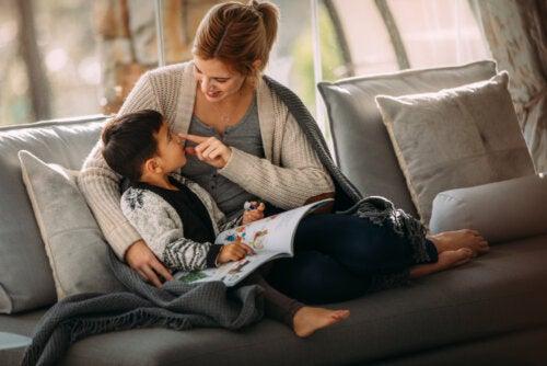 Madre e hijo leyendo uno de los libros infantiles sobre inmigración en el sofá.