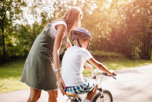 Madre ayudando a su hijo a montar en bicicleta.