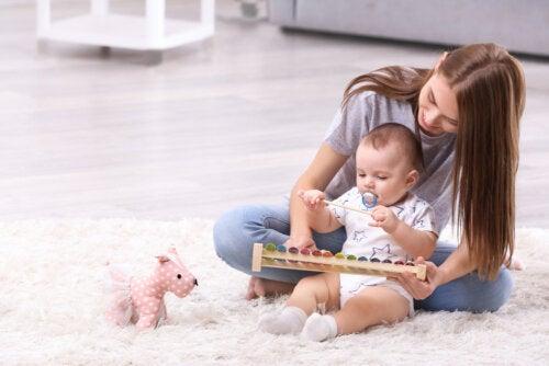 Mamá jugando con su bebé y haciendo ejercicios para su desarrollo.