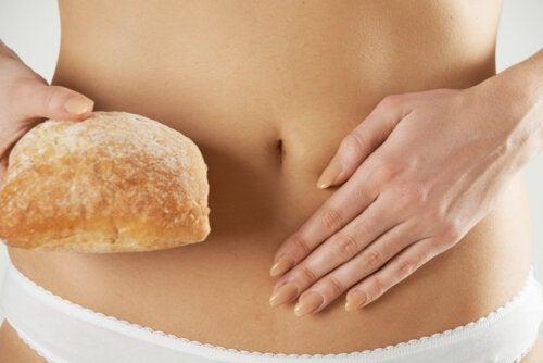 Mujer con un pan de la mano y dolor de barriga debido a la sensibilidad al gluten no celiaca que padece.