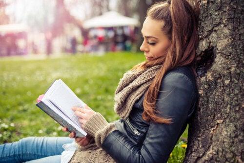 Chica joven leyendo uno de los libros para adultos apoyada en un árbol.