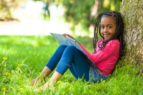 Niña apoyada en un árbol leyendo un libro.