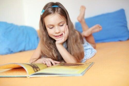 Niña leyendo en la cama un libro para recuperar el hábito lector.