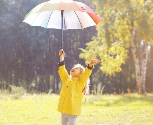 Niña disfrutando bajo la lluvia con un paraguas y un chubasquero.