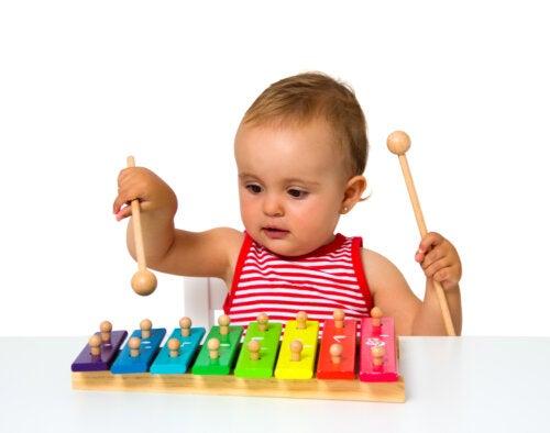 Niña tocando el xilófono porque la música es beneficiosa para el desarrollo cognitivo infantil.