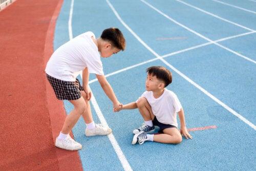 Niño ayudando a otro que se ha caído en las pistas de atletismo.