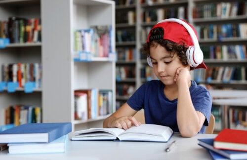 Niño leyendo un libro en la biblioteca con los auriculares puestos.