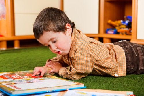 Niño leyendo en el suelo uno de los libros sobre las relaciones entre hermanos.