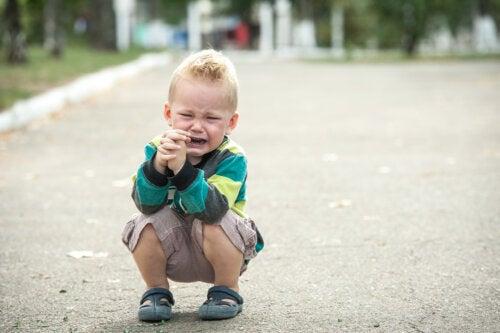 Niño con una rabieta llorando en medio de la calle.